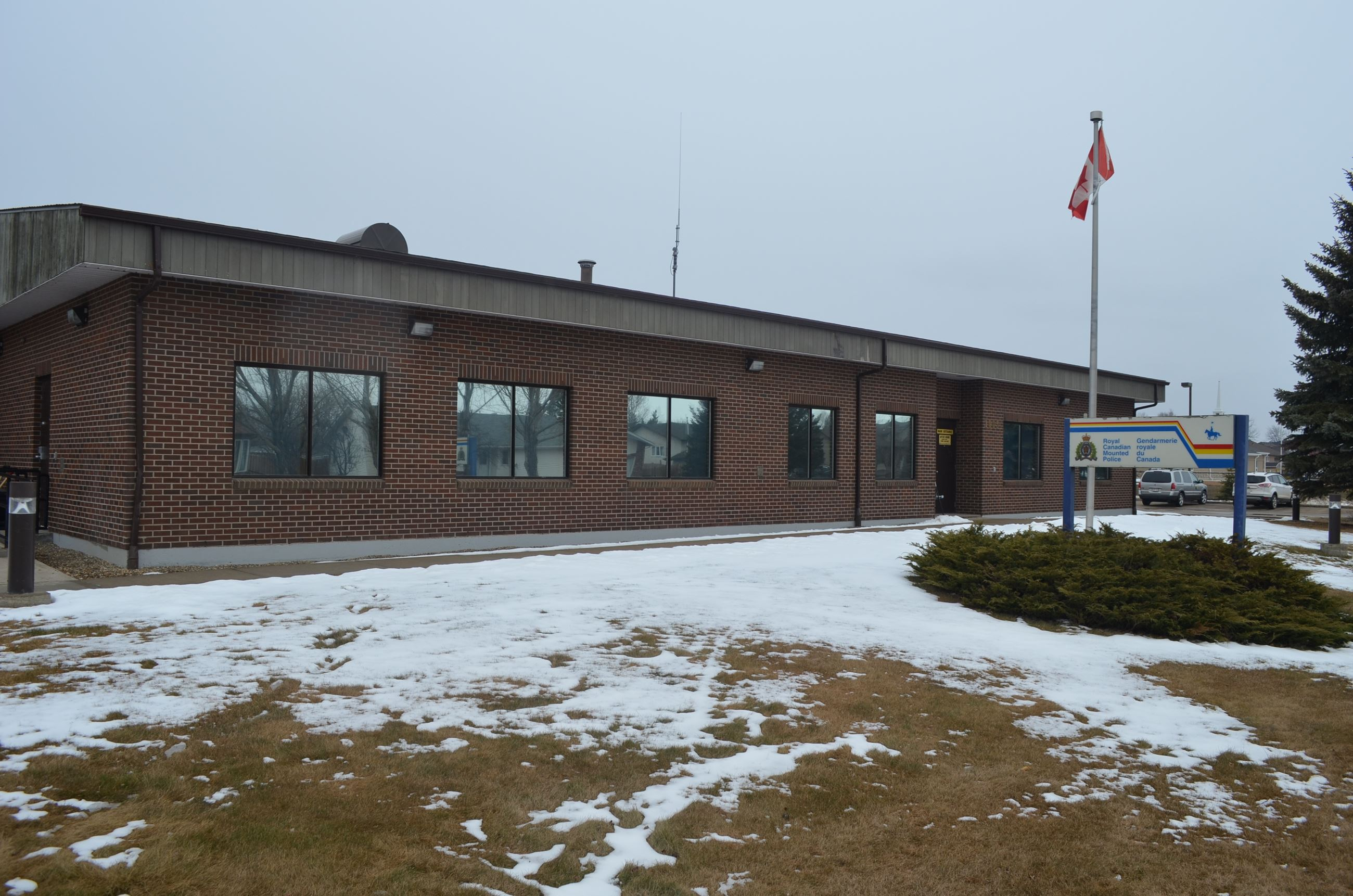 The front of the Royal Canadian Mounted Police building with snow on the ground in front of it.