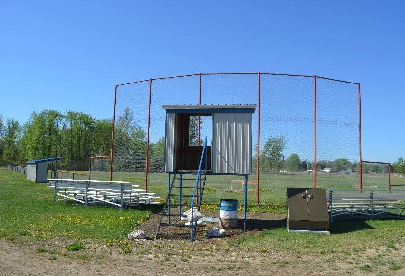 A grass ball field with a blue and white spectator booth and bleachers.
