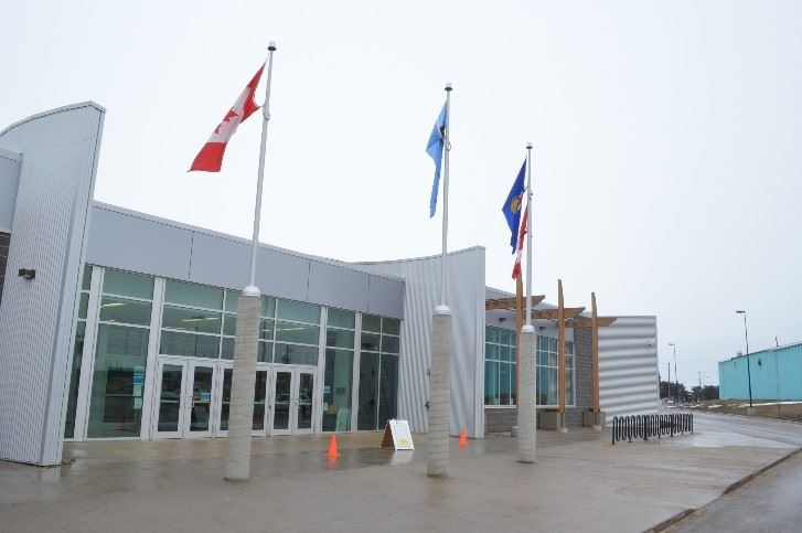 The modern facade of the Multi Recreation Centre, with flags waving above.